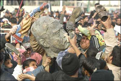 Iraqi Shiite Muslim men beat a bust of ousted president Saddam Hussein in Sadr City, Baghdad